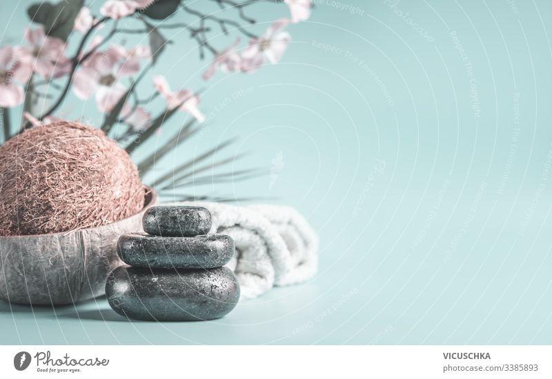 Zen-Steine mit Kokosnuss und Handtüchern auf hellblauem Hintergrund mit Blumen. Entspannender Schönheitstag. Spa-Konzept Licht Tag niemand Erholung Nahaufnahme