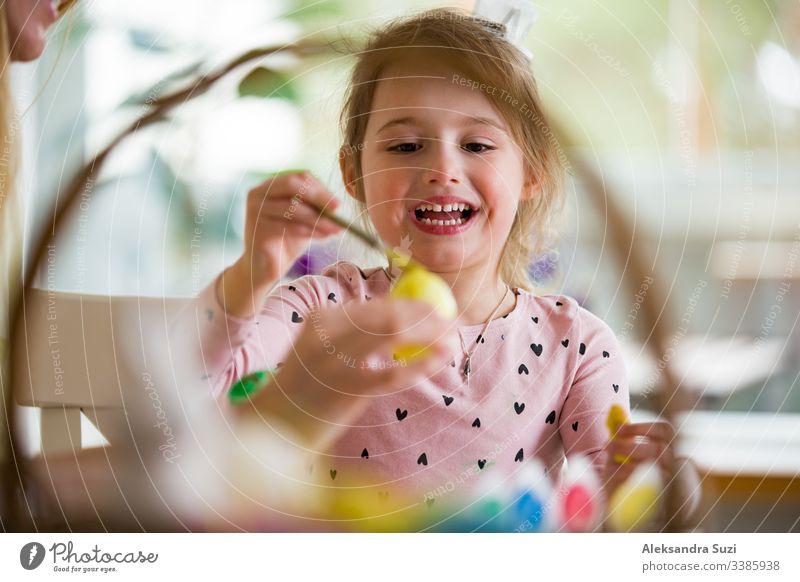 Eine Mutter und eine Tochter feiern Ostern und bemalen Eier mit dem Pinsel. Eine glückliche Familie, die lächelt und lacht. Ein süßes kleines Mädchen in Hasenohren, das den Feiertag vorbereitet.