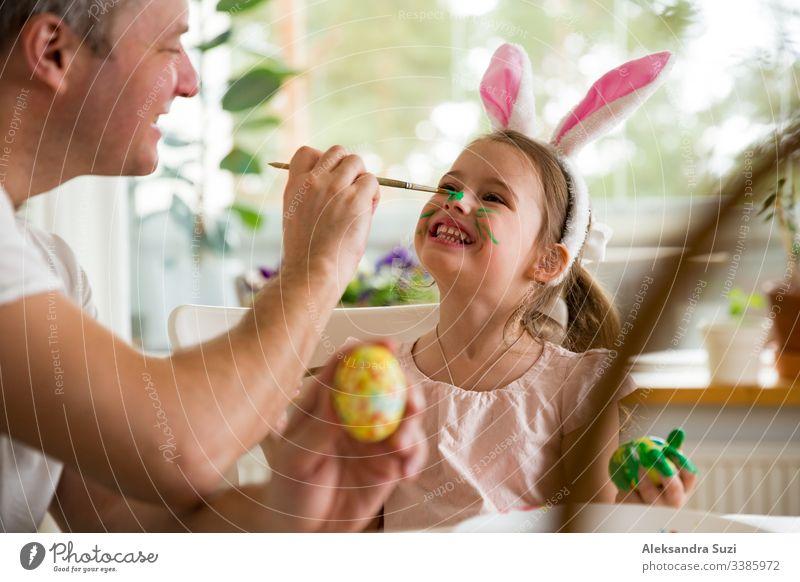 Ein Vater und eine Tochter feiern Ostern und bemalen Eier mit dem Pinsel. Eine glückliche Familie, die lächelt und lacht, die sich auf das Gesicht gemalt hat. Ein süßes kleines Mädchen in Hasenohren, das den Feiertag vorbereitet.