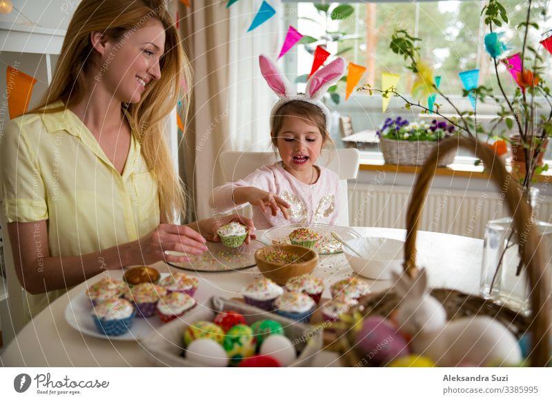 Mutter und Tochter feiern Ostern, kochen Muffins, mit Glasur überzogen. Fröhlicher Familienurlaub. Süßes kleines Mädchen in Hasenohren. backen offen Feier Kind