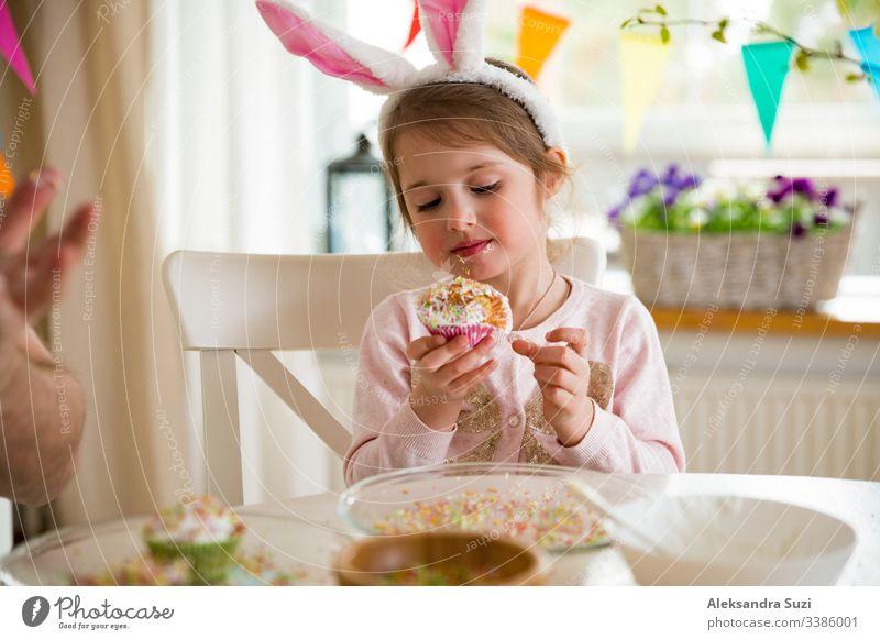 Vater und Tochter feiern Ostern und essen mit Glasur überzogene Törtchen. Fröhlicher Familienurlaub. Süßes kleines Mädchen in Hasenohren. Wunderschön dekorierter Raum