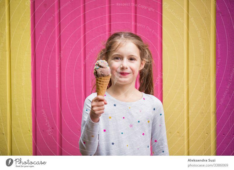 Süßes kleines Mädchen isst Schokoladeneis. Lächelnd und lachend. Bunte rosa und gelbe Wand im Hintergrund. Leuchtendes Sommerkonzept schön hell Café offen