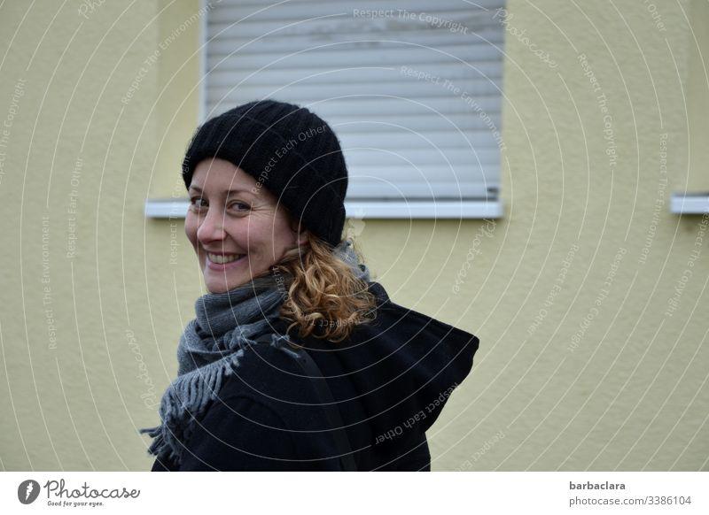 Das Leben vor einer tristen Wand Rolladen Frau lachen Haus Locken Mütze Mantel schwarz Fensterbank grau herbstlich