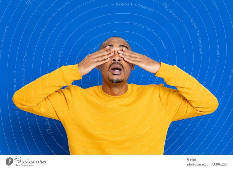 Afrikaner mit gelbem Trikot schwarz Typ überrascht aufregend verrückt Glück Emotion Überraschung Deckung Auge blind zugeklappt blau Erwachsener Menschen Person