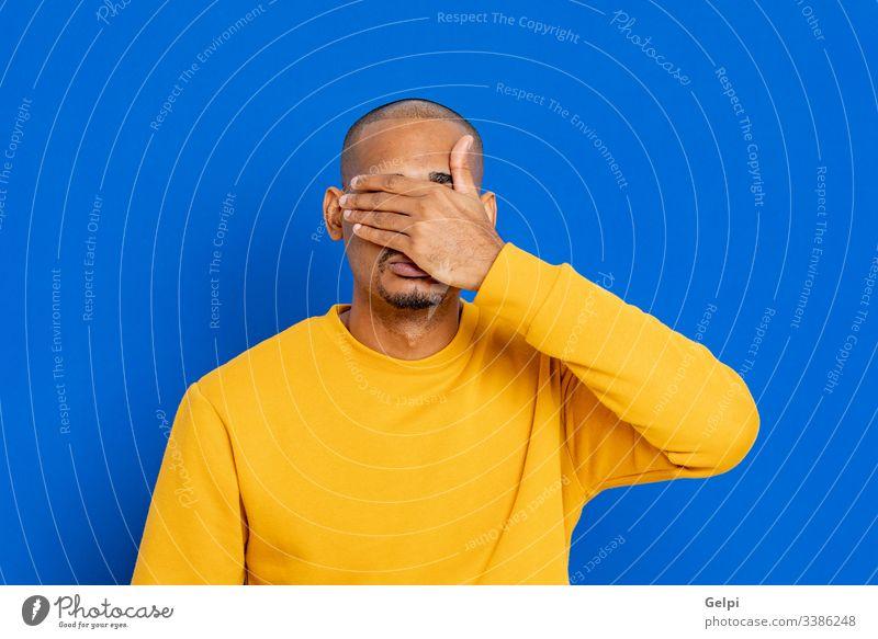 Afrikaner mit gelbem Trikot schwarz Typ Deckung Gesicht Stille Wut traurig Angst verängstigt Depression Scham Terror Negativität verbieten ängstlich furchtbar