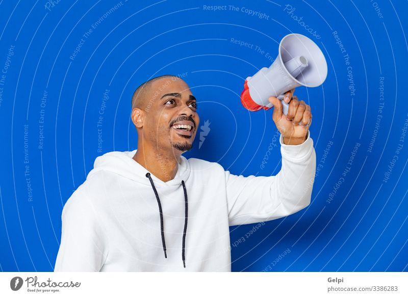 Afrikanischer Typ mit weißem Sweatshirt schwarz blau Megaphon Lautsprecher laut Redner Schreien ankündigen Stimme schreiend Kommunizieren Ankündigung Anzeige