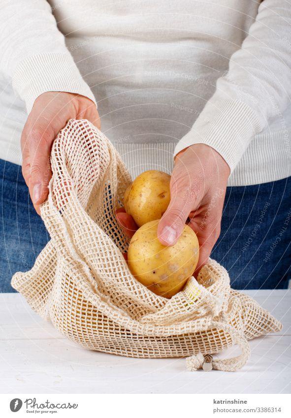 Frau legt frische Kartoffeln in einen Textilbeutel keine Verschwendung Konzept Abschluss setzen Hände gesichtslos Tasche Gemüse Landwirte abschließen null