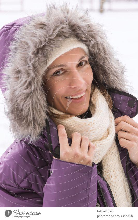 Frau mit Winterjacke und Kaputze frau erwachsene gesicht portrait schal fell mantel kaputze winter kalt hände lachen fröhlichkeit freundlich Blick in die Kamera
