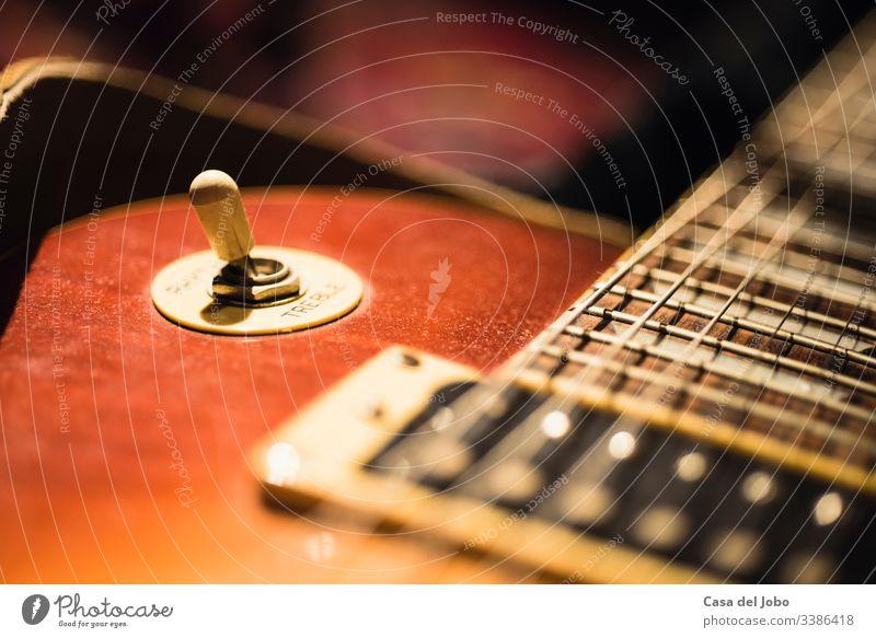E-Gitarre auf dunklem Hintergrund Musik rot Sonnenbrand Felsen Instrument Musical Jazz elektrisch weiß Holz Nahaufnahme spielen Schnur Gerät schwarz Konzert