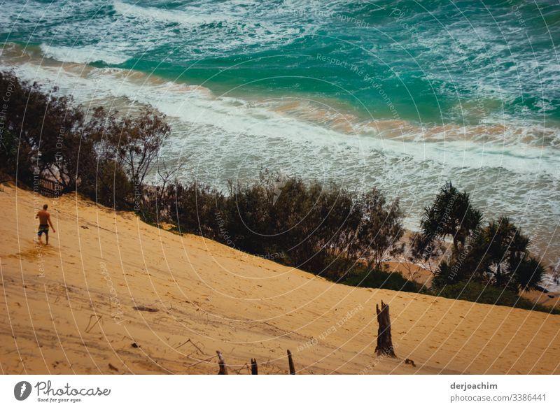 Ein Mann geht die Sanddüne hinunter zum Meer Wasser Brandung Wellen Gischt Natur Außenaufnahme Küste Farbfoto Urelemente Textfreiraum oben Umwelt wild Tag blau