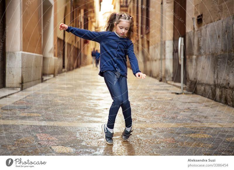 Ein süßes kleines Mädchen tanzt auf der Straße der Stadt. Enge Straßen der Altstadt von Palma de Mallorca. aktiv schön sorgenfrei Kind Kindheit Kinder Großstadt