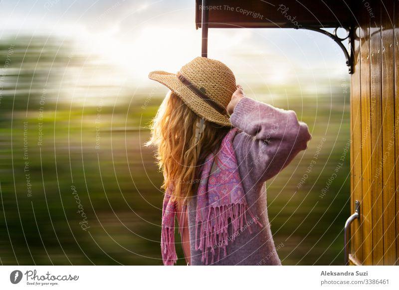 Junge Frau mit Strohhut reist mit einem Retro-Holzzug. Sonnenuntergangslandschaft, Wind in blonden Haaren. Mädchen lächelt fröhlich. Mallorca, Spanien.