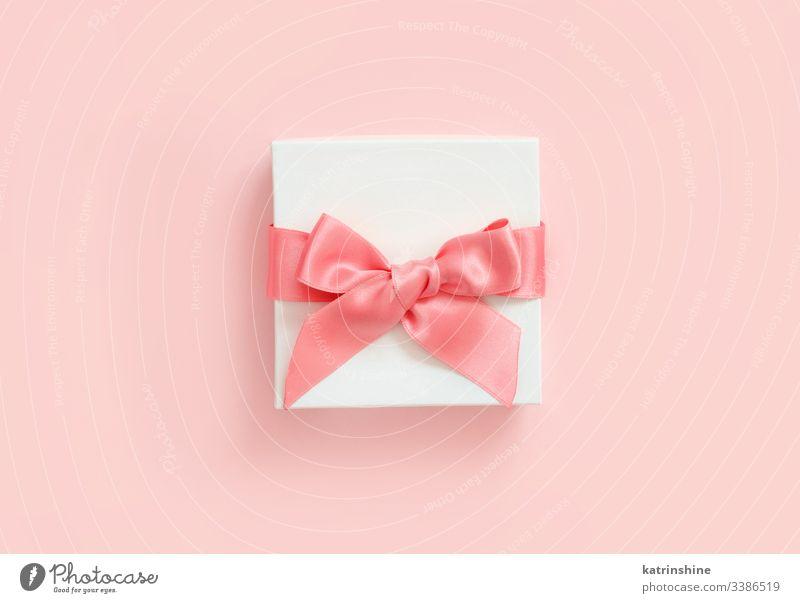 Weiße Geschenkverpackung mit Schleife auf hellrosa Hintergrund weiß Bändchen Liebe romantisch Draufsicht oben präsentieren Konzept kreativ Tag Dekor