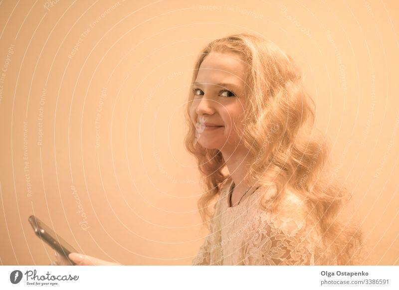 Teenager-Model..Hübsches blondes Mädchen mit Smartphone auf hellem Hintergrund. Platz für Text. Frau jung attraktiv Porträt Dame Beteiligung Lächeln Mobile