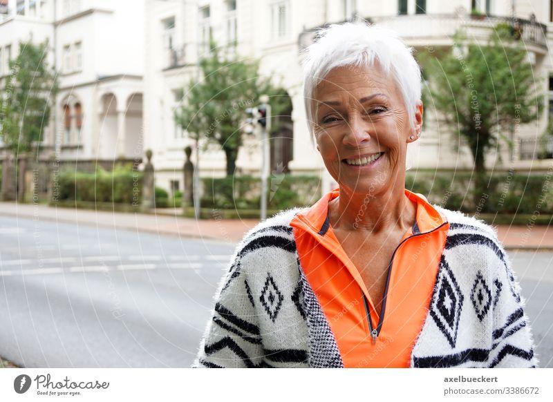 glückliche reife Frau auf der Straße Senior Dame Glück Lächeln außerhalb Erwachsener Großstadt urban Bestseller 60 trendy sportlich kurz weiß Behaarung