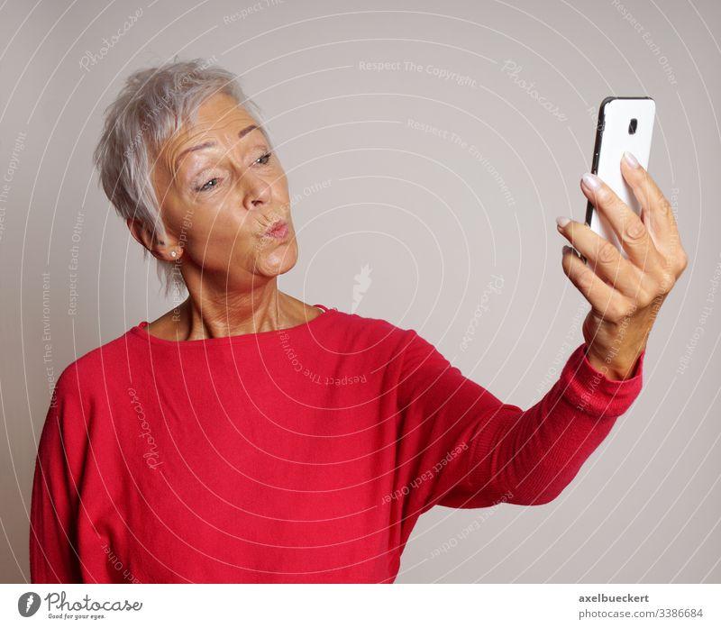 ältere Frau macht Duckface für Selfie mit Smartphone Selbstportrait Kussmund Senior Fotokamera Telefon Dame Erwachsener lustig Ausdruck 60 trendy selbstbewusst