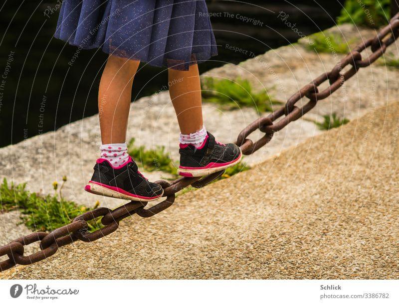 Junges Mädchen balanciert über eine schwere Eisenkette Beine Rock junges Mädchen balancieren diagonal Schwache Tiefenschärfe Textfreiraum unten