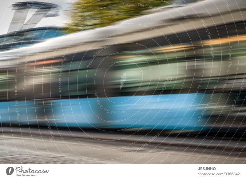 fahrende Straßenbahn mit Bewegungsdynamik Bewegungsunschärfe fahrende s-bahn straßenbahn Tag vorbeifahren bewegen blau grau grün schnell rasend schnell