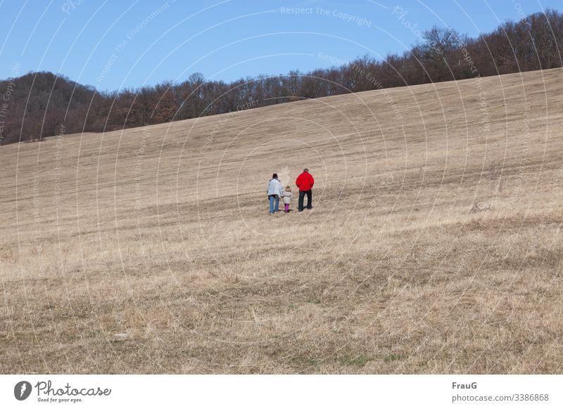 Spazierengehen bergauf bergauf gehen Menschen Frau Mann Kind Mädchen Hände in Taschen Hand halten Jacken Wald Wiese Frühling spazierengehen Spaziergang Natur