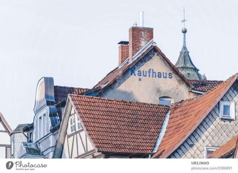 Dächer alter Fachwerkhäuser und Giebel mit der Aufschrift Kaufhaus Dach Baustein Fachwerkhaus Turmspitze Schornsteine Dorf Altstadt Gedeckte Farben High Key Tag
