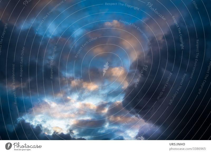 dunkle farbenfrohe Unwetterwolken Wolken wolkig Himmel blau Gewitterwolken rosa menschenleer starke Schärfentiefe Froschperspektive Textfreiraum rechts