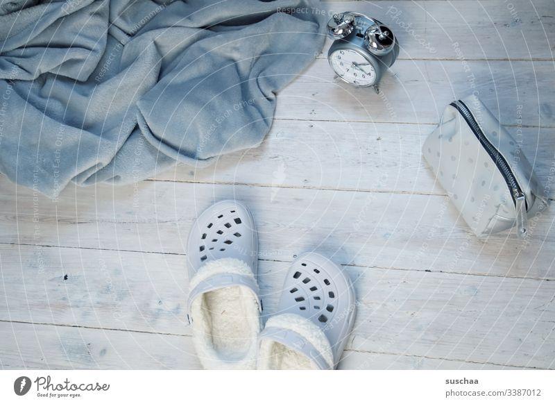 graue kuscheldecke mit hausschlappen, wecker und schminktäschchen auf weissem holzfußboden Decke Kuscheldecke Wohnen Zuhause Häusliches Leben Grautöne