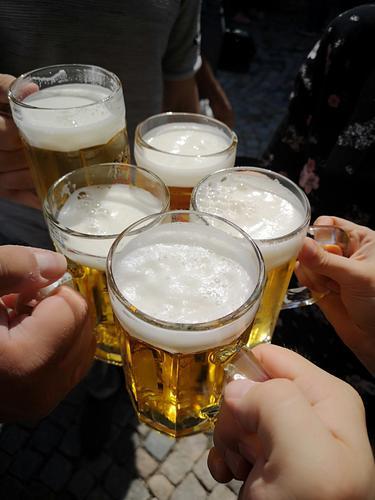 Prost! Mit einem vollen Glas Bier Außenaufnahme Freundschaft trinken Biergarten Alkohol Freude Farbfoto Tag Zuprosten Schwache Tiefenschärfe Party