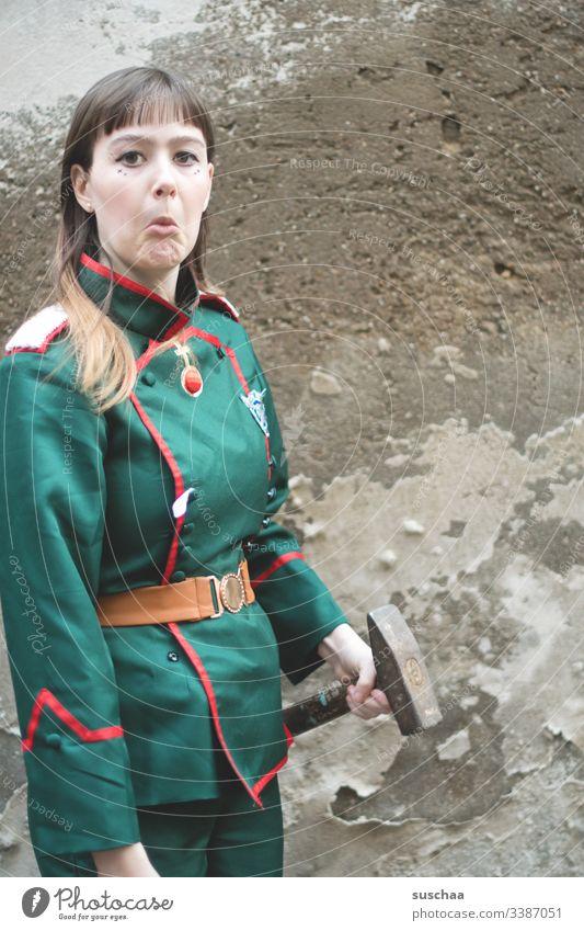 teenager steht vor mauer mit uniform und hammer in der hand Fotochallenge Jugendliche Teenager Mauer Wand Uniform Hammer Werkzeug Gesicht Grimasse Kostüm