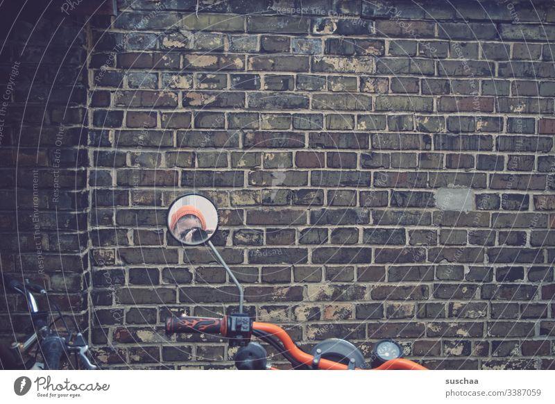 fotografin spiegelt sich im motorradspiegel vor mauer Mauer Motorrad Motorradlenker Motorradspiegel Spiegel Frau Fotografin Außenaufnahme Straße Kleinmotorrad