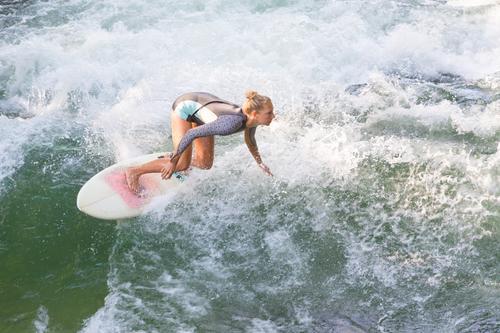 Attraktives, sportliches Mädchen surft auf der berühmten künstlichen Flusswelle im Englischen Garten, München, Deutschland. Surfer Brandung Surfbrett Surfen