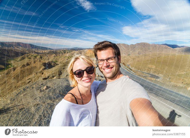 Aktives, glückliches Paar, das sich auf Reisen in das Hochgebirge des Atlas, Ouarzazate, Marokko, begibt. Selfie Abenteuer Porträt Spaß wüst Architektur
