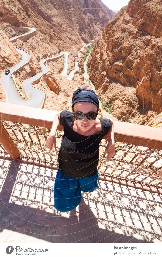 Das Bild einer Touristin, die sich auf einer Terrasse auf einer kurvenreichen Straße im Dades-Tal, Atlas-Gebirge, Marokko, entspannt. Schlucht Frau Abenteuer