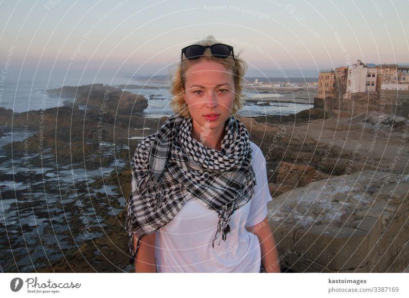 Weibliche Reisende steht auf der Stadtfestungsmauer von Essaouira, Marokko im Sonnenuntergang. Reisender Abenteuer reisen Mädchen Entdecker Frau Lifestyle