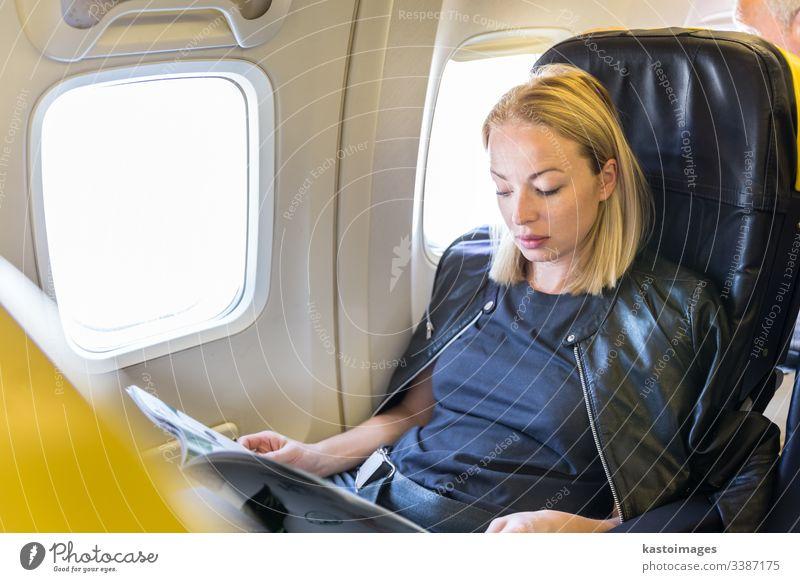 Frau liest während des Fluges im Flugzeug eine Zeitschrift. Ebene Air Fluggerät Verkehr Transport reisen Ausflug Sitz Passagier Mädchen Magazin Innenbereich