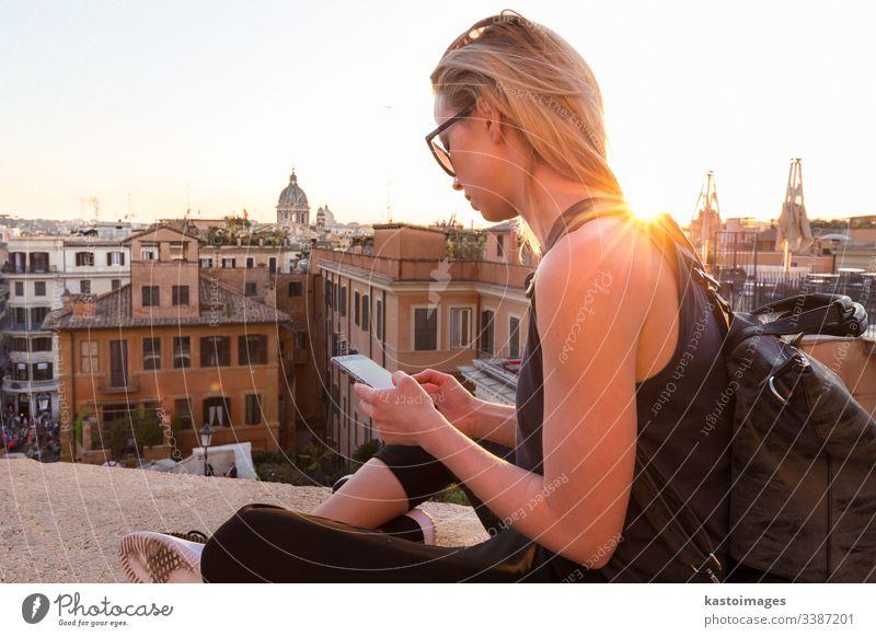 Touristin, die eine Handy-Reise-App in der Nähe der Piazza di Spagna nutzt, dem Wahrzeichen des Platzes mit den spanischen Stufen in Rom, Italien bei Sonnenuntergang.