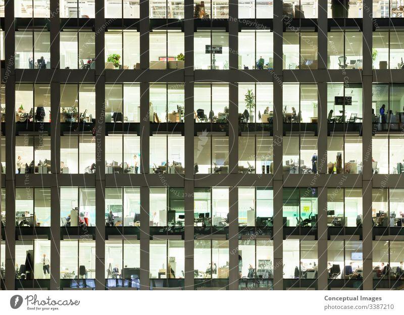 Modernes Bürogebäude in der Abenddämmerung, das die täglichen Aktivitäten der Arbeiter offenbart Bürogebäude außen überarbeitet Business Menschen Ehrgeiz
