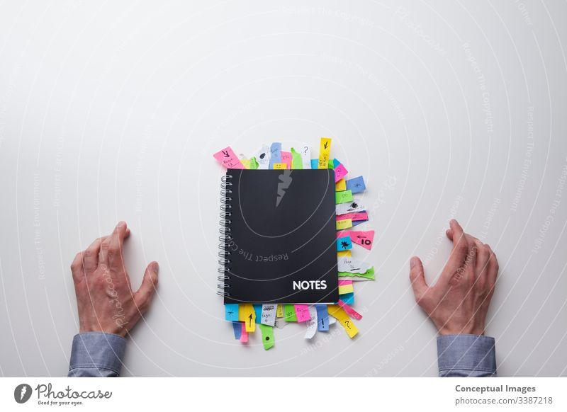 Draufsicht eines Mannes vor einem Notizblock voller Haftnotizen Klebstoff Analyse Ernennung Brainstorming Business beschäftigt Zusammenarbeit Farbe Konzepte