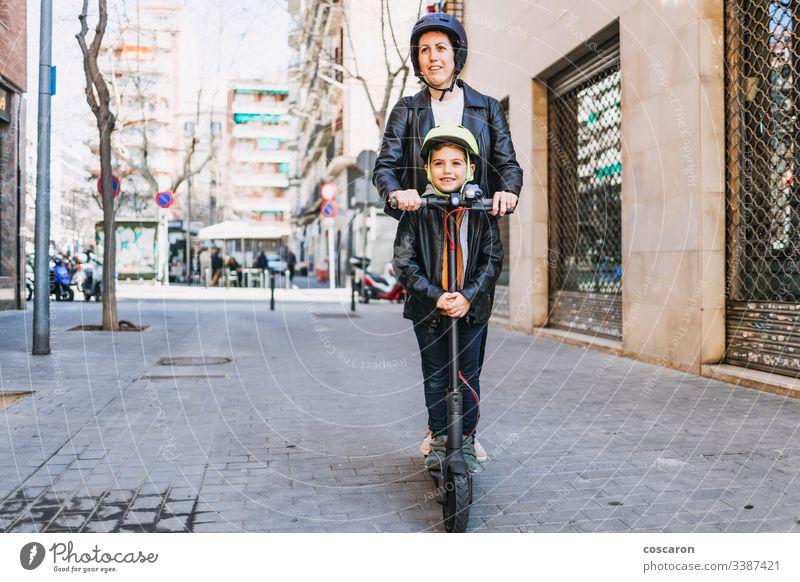 Mutter und Sohn auf einem Elektroroller mit Helm aktiv Junge lässig Kind Großstadt Tag E-Roller Öko elektrisch Europa Familie Frau Spaß Generation Schutzhelm