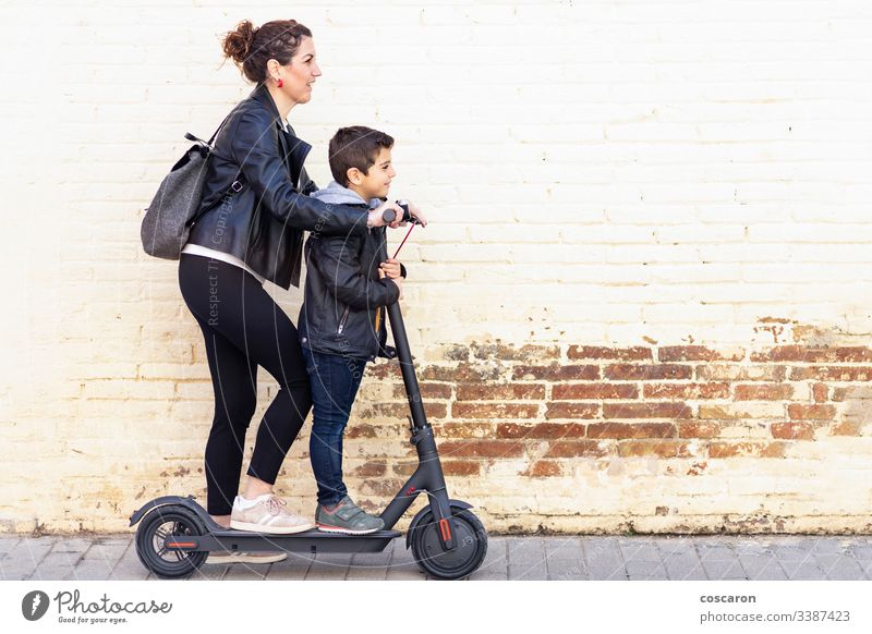 Mutter und Sohn auf einem Elektroroller aktiv Junge lässig Kind Großstadt Tag E-Roller Öko elektrisch Europa Familie Frau Spaß Generation Kick Kickroller