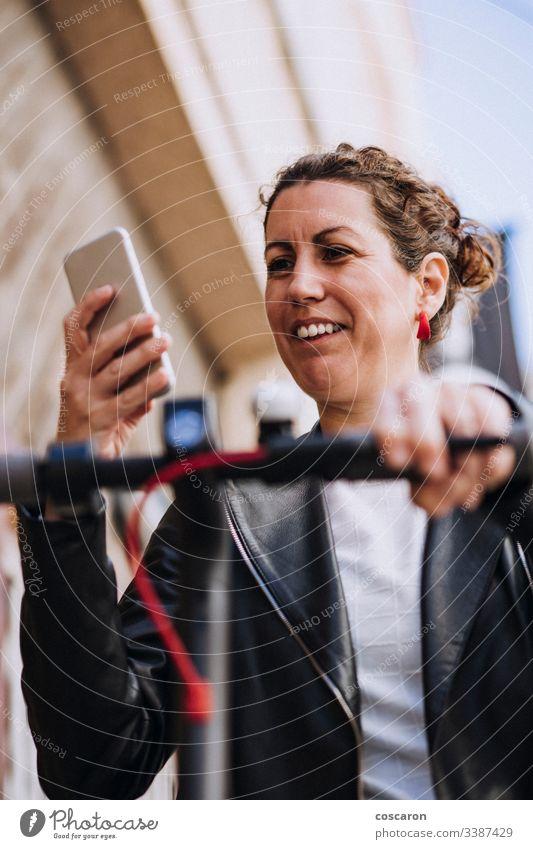 Frau mittleren Alters, die auf seinem Elektroroller fährt und auf ihr Handy schaut. aktiv Aktivität App Herbst Hintergrund schön Fahrrad blond Buchung Autos