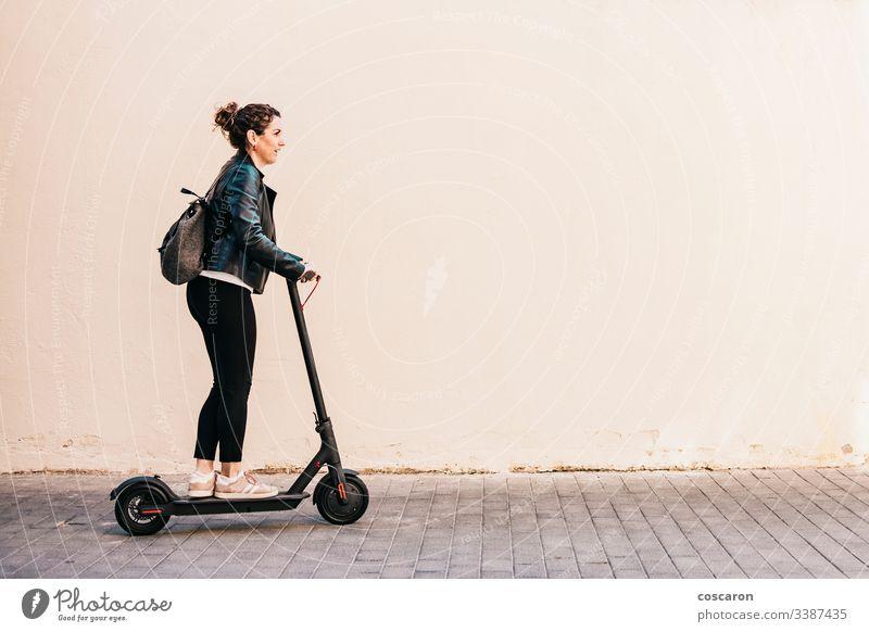 Frau mittleren Alters auf einem Elektroroller aktiv Erwachsener allein attraktiv Hintergrund Holzplatte Business heiter Großstadt fahren e-Scooter Öko