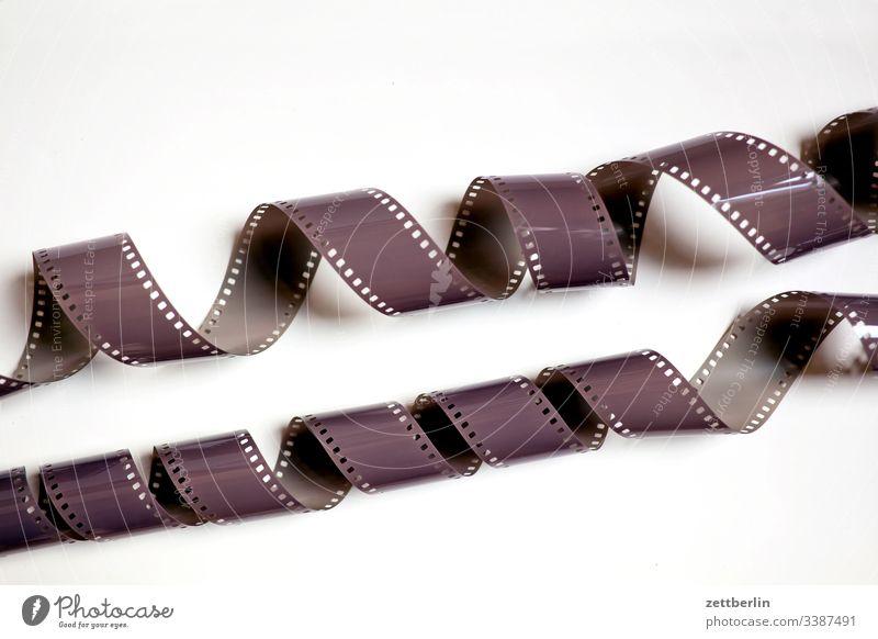 Film zelluloid kleinbildfilm rollfilm meterware belichtung belichtet foto fotografie analog filmmaterial perforation abgewickelt spirale verdreht menschenleer