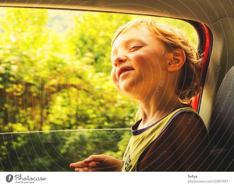 Kleiner kaukasischer Junge, der Sonne und Wind genießt und in einem Auto mit offenem Fenster fährt. wenig Kind PKW reisen Glück Haut Emotion Moment Behaarung