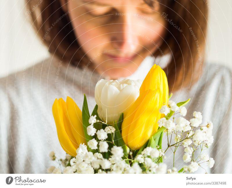 Frau hält Blumenstrauß aus gelben und weißen Tulpen. Frauen, Muttertagskonzept. Haufen Tag geben Frühling Ostern Hände geblümt Dame März Geschenk Einladung Gruß