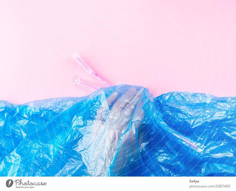 Plastikstrohhalme, die ins Meer geworfen werden, dargestellt durch eine blaue Plastiktüte und die Hand unter Wasser. Verschmutzungskonzept auf rosa Hintergrund.