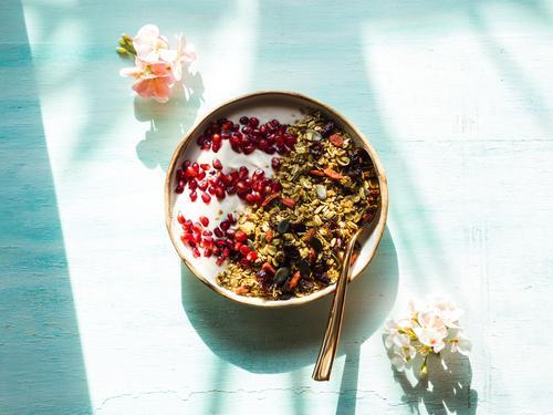 Hausgemachte Müslimaschüssel mit Granatapfelkernen, Matcha-Müsli mit Hafer und Trockenfrüchten, Nüsse auf türkisem Hintergrund mit rosa Blüten. Frühstück lecker