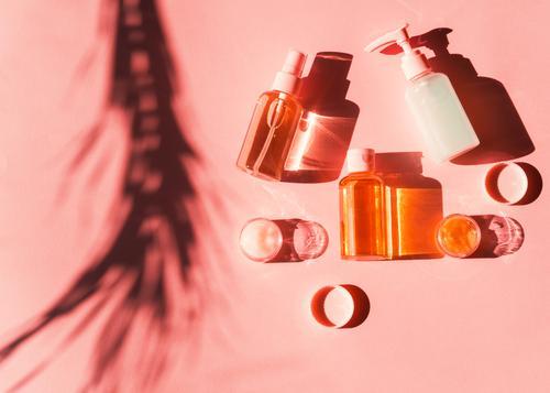 Verschiedene Kosmetikprodukte in Flaschen und Minidosen auf rosa Koralle. Flacher Schuss in hartem Licht mit Pflanzenschatten. Haut Produkte Schatten