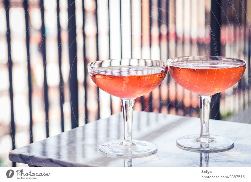 Zwei Kristallstielgläser mit Rosenwein auf Marmortisch im Freien. Aperitifzeit Wein Roséwein weiß Glas Murmel Party rosa trinken Abendessen Tisch Reichtum Licht