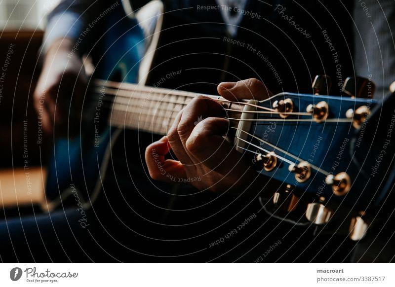 Gitarre gitarre westerngitarre gitarrenspieler griffbrett stahlsaiten blau hände hand mann greifen akkorde nahaufnahme