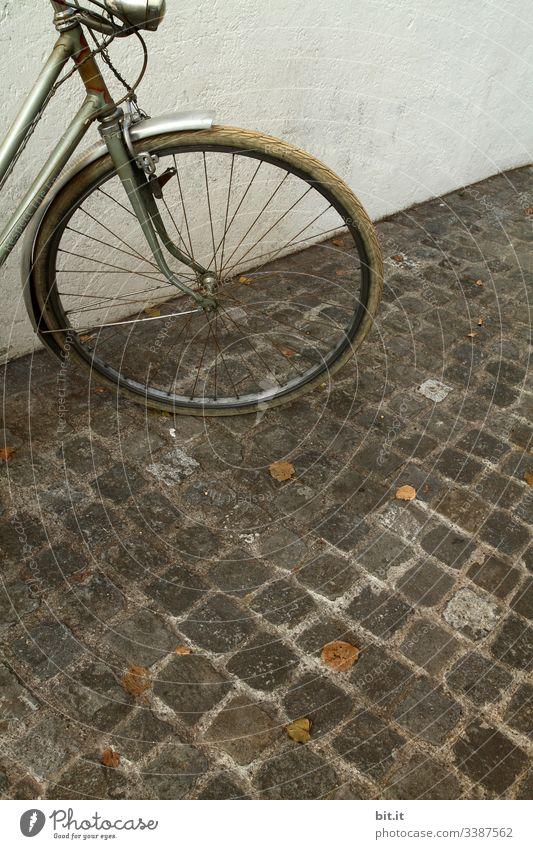 alt l altes, nostalgisches Rad im Retro-Stil, steht geparkt vor weisser, heller Hauswand auf Kopfsteinpflaster. Vorderteil, Lampe, Licht, Reifen von grauem Rad parkt in der Stadt.Diebstahlgefahr von altem Fahrrad, ungesichert, nicht abgeschlossen im Herbst